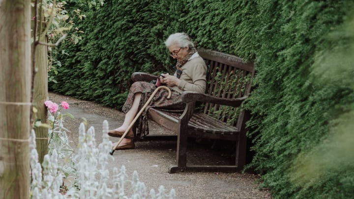 elderly woman sitting alone on park bench with her cane