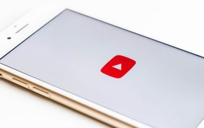 smartphone laying on table with YouTube logo on the screen