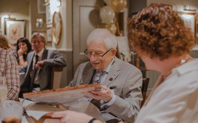 elderly gentleman unwrapping a birthday present