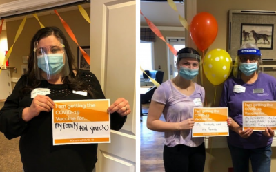 """team members at Barrington Place Alzheimer's Special Care Center displaying their """"I am vaccinated"""" signs"""