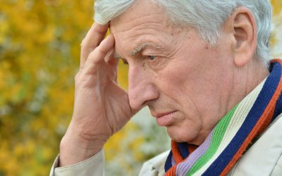 Portrait of Pensive elderly man on the background of autumn leaves